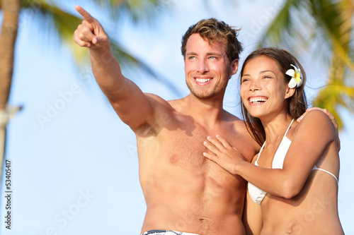 Couple on beach happy in swimwear, man pointing