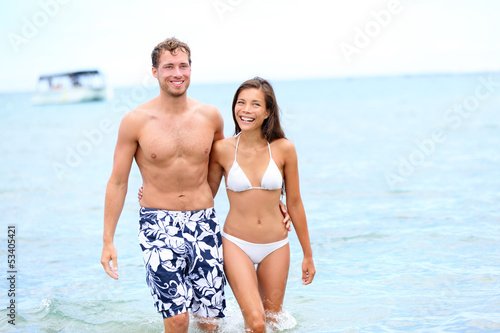 Beach couple in love walking happy in water