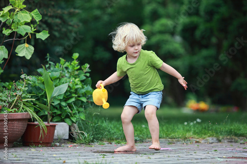 Little caucasian  barefoot girl playing with watering can