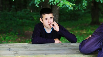 The boy takes a cigarette offered