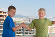 Two smiling boys are shake hands on background of building