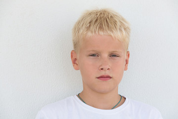 Portrait of young boy with focused look in white t-shirt