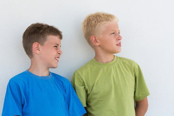 Two boys in colored T-shirts somewhere looking
