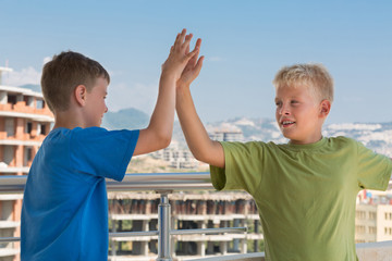 boys are greet each other on background of building