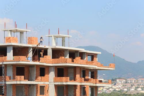 Workers erect balconies from brick in building at top floor