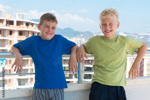Two smiling boys are on background of building