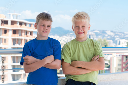 Two boys with hands on chest are on background of building