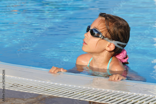 Smiling cute girl in goggles swimming in pool