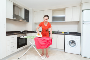 Smiling housewife ironing laundry in middle of kitchen