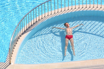 boy in the red trunks floating in the pool face up