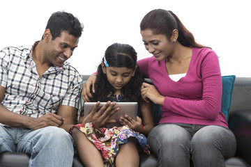 Happy Indian family at home using digital tablet