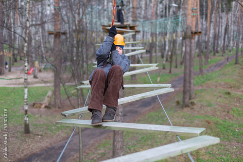 Little climber goes zigzag obstacle holding safety rope