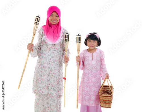 malay sisters with oil lamp during hari raya festival