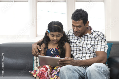 Indian father and daughter using digital tablet together.