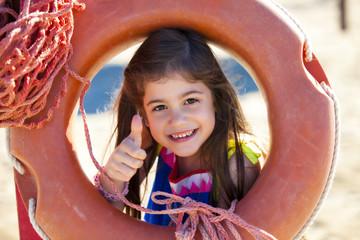 Bella bambina positiva e sorridente con salvagente