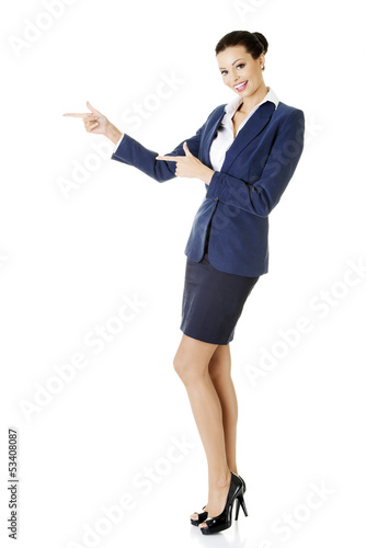 Happy young business woman pointing on copy space