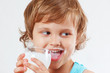 Beautiful blonde child drinking a fresh milk on white background