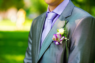 Closeup groom's buttonhole with delicate purple flowers