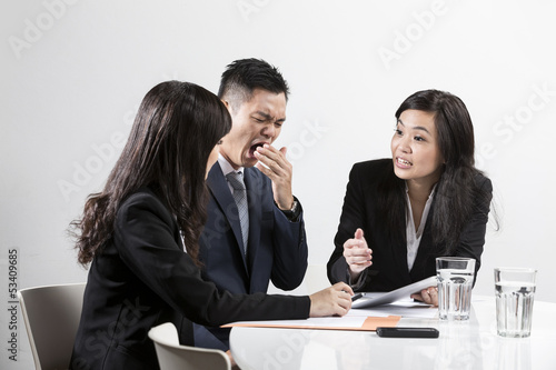 Chinese businessman yawning during business meeting