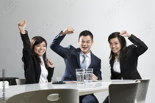 Happy Chinese business people celebrating in a meeting.