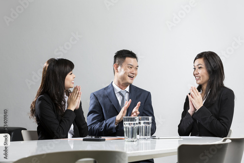 Happy Chinese business people applauding in a meeting.