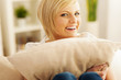 Beautiful and smiling woman embracing pillow .