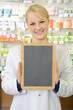 Freundliche Apothekerin hält leere Tafel