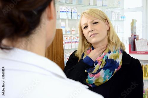 Junge Frau in Apotheke hat Halsweh