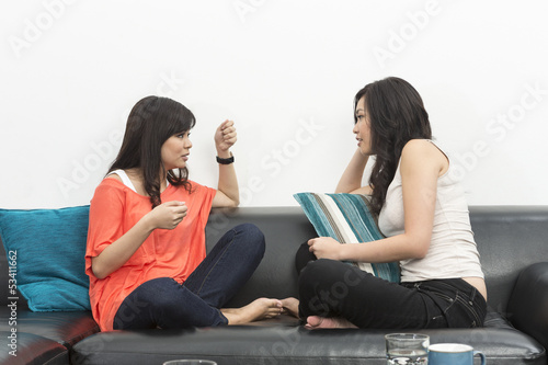 Two Chinese friends sitting on couch
