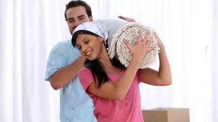 Couple holding carpet on shoulders