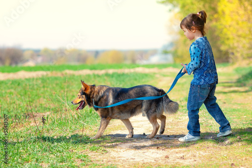 Little girl with dog walking outdoors