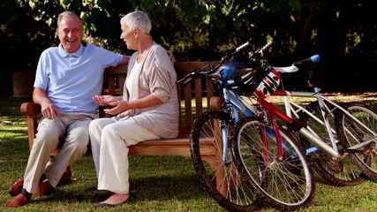 Mature couple talking together in a park next to mountain bikes