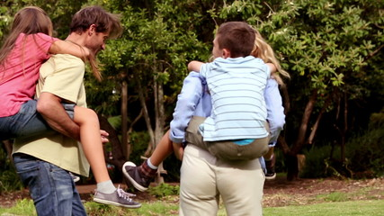 Parents giving piggy back rides to their children