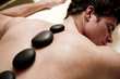 Young man doing hot stone therapy