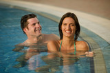 Young couple relaxing in swimming pool at health club