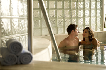 Young couple relaxing in whirlpool in spa