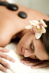Young woman doing hot stone therapy