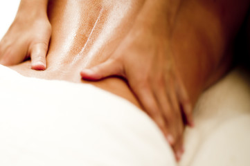 Hands massaging woman's lower back.