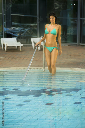 Young woman stepping into swimming pool