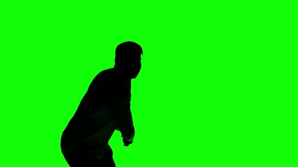 Silhouette of a man playing tennis on green screen