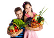 Smiling kids with vegetables in basket