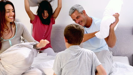 Family playing together with pillows