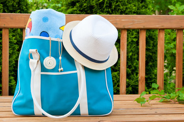 Blue bag with towel and hat for outdoor pool or beach weekend.
