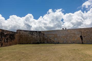 two people sit on wall at  El Morro in Old San Juan, PR