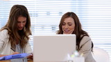 Two women laugh by working