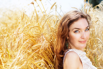 Portrait to the beautiful girl in the field with a rye