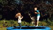 Cheerful siblings having fun with a ball on a trampoline