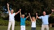Grandchildren and grandparents jumping together in a park