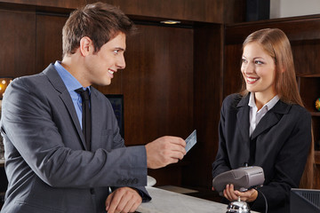Mann im Hotel bezahlt mit Kreditkarte