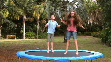 Siblings jumping on a trampoline